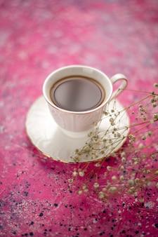 ピンクの机の上の皿の上のカップの中のお茶の正面図