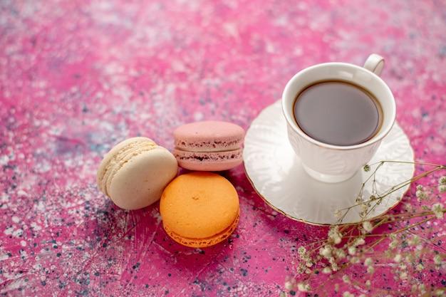 Вид спереди чашка чая внутри чашки на тарелке с французскими макаронами на розовом столе