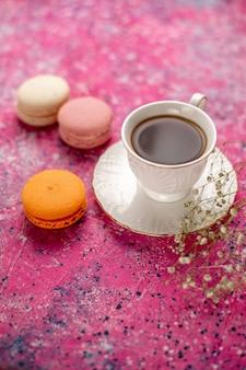 분홍색 책상에 프랑스어 마카롱과 함께 접시에 컵 안에 차의 전면보기 컵