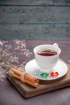 暗いスペースにプレートが付いたガラス カップの中にお茶を入れた正面図