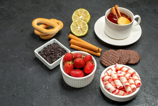 Чашка чая с печеньем и сладостями, вид спереди