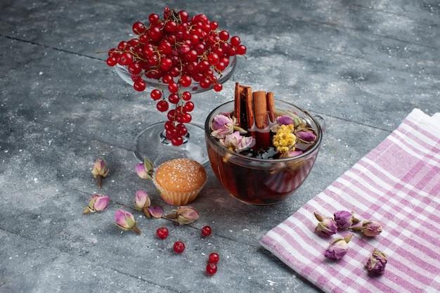 Вид спереди чашка чая с пирожным с корицей и свежей красной клюквой на сером столе сахарный чай с фруктами