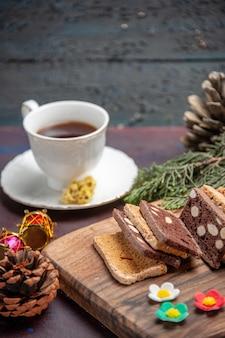 Вид спереди чашка чая с кусочками торта на темном письменном столе, печенье, сахарное печенье, чай