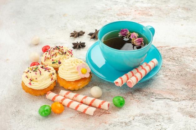 白い机の上のキャンディーとケーキとお茶の正面図ティーデザートビスケットケーキパイ