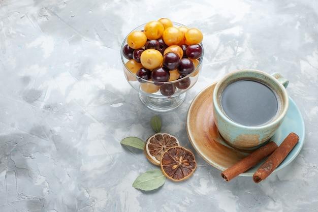 白い背景の上のシナモンとチェリーとお茶の正面図はお茶シナモンレモン色を飲みます