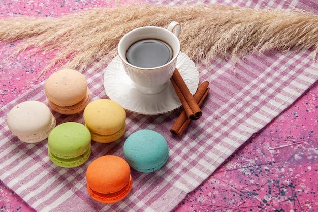 ピンクのデスクケーキビスケットクッキースイートシュガーにシナモンとフレンチマカロンを添えた正面図のお茶