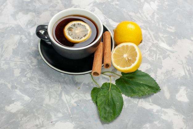 Чашка чая с корицей и лимоном на белой поверхности, вид спереди