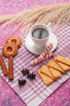 분홍색 책상 비스킷 설탕 달콤한 빵에 계피 쿠키와 크래커와 차의 전면보기 컵