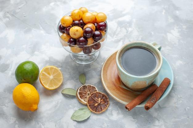 シナモンレモンと白い机の上のチェリーとお茶の正面図はお茶シナモンレモン色を飲みます