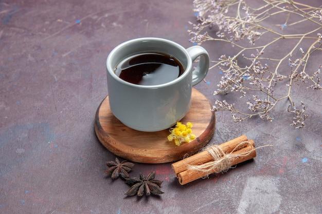 Вид спереди чашка чая с корицей на темно-фиолетовом фоне пить чай сладкого цвета