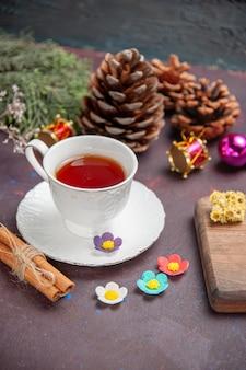 Вид спереди чашка чая с корицей на темном пространстве