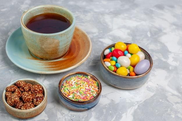 明るい白い机の上にカラフルなキャンディーとお茶の正面図