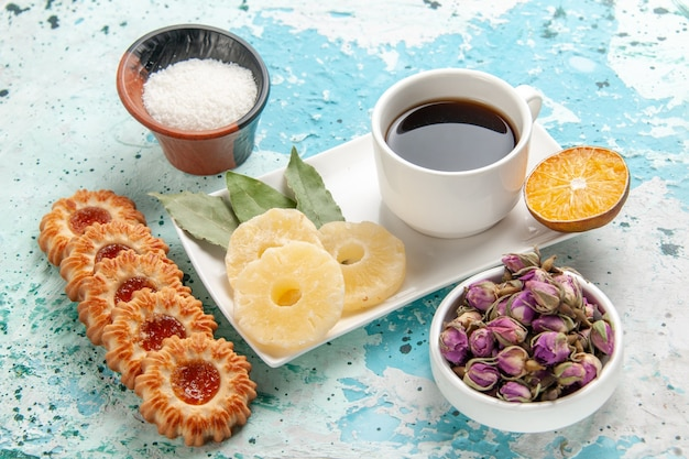 Вид спереди чашка чая с печеньем и сушеными кольцами ананаса на голубой поверхности