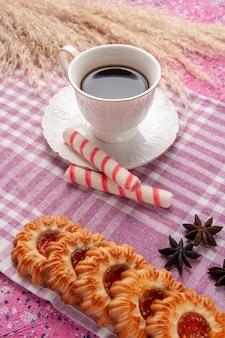 분홍색 책상 비스킷 설탕 쿠키 달콤한 쿠키와 스틱 사탕 차 전면보기 컵