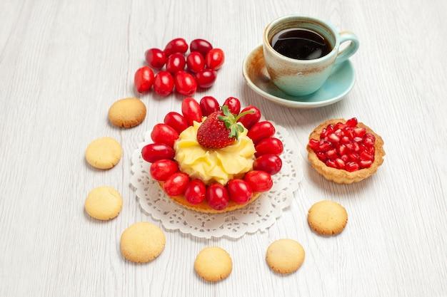 クッキークリームケーキと白い机の上の果物とお茶の正面図お茶のデザートケーキ