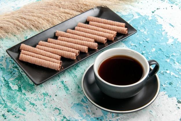 Вид спереди чашка чая с печеньем на синей поверхности