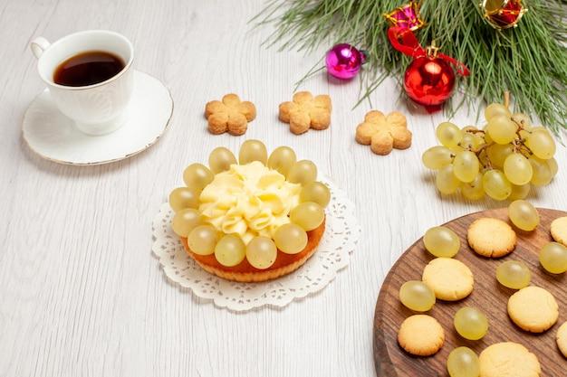 白い机の上のクリームケーキとブドウとお茶の正面図フルーツティーデザートクリームビスケットケーキ