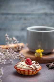 Вид спереди чашка чая с вкусным тортом на темном фоне чайный торт сладкий пирог печенье бисквит