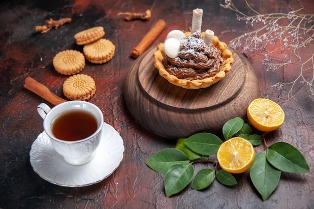 暗い背景においしい小さなケーキとお茶の正面図