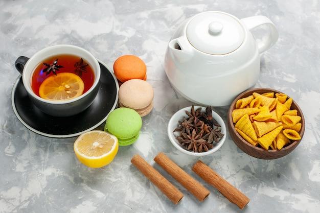 Чашка чая с французскими макаронами и корицей на белой поверхности, вид спереди