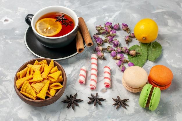 Чашка чая с французскими макаронами на светло-белом столе, вид спереди