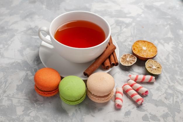 Чашка чая с французскими макаронами на светлом столе, вид спереди