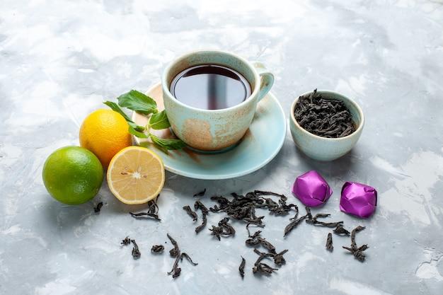 Вид спереди чашка чая со свежими лимонными конфетами и сушеным чаем на белом столе, чай фруктовый цвет цитрусовых