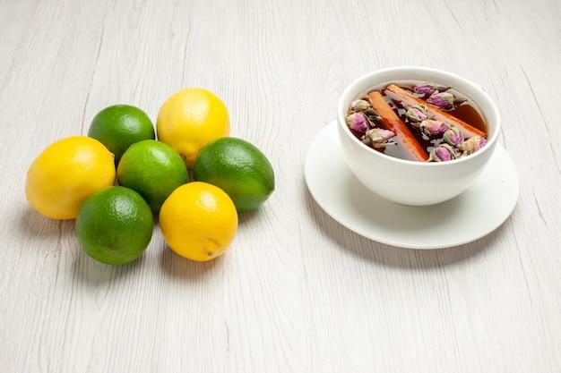 白い机の上の新鮮なレモンとお茶の正面図ティーフルーツ柑橘系の色