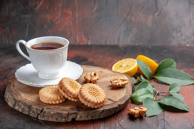 暗い背景にレモンとクッキーとお茶の正面図