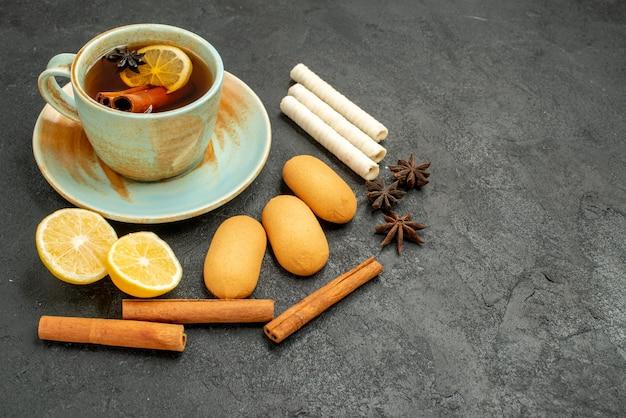 Вид спереди чашка чая с лимоном и печеньем на сером столе, печенье, сладкое печенье