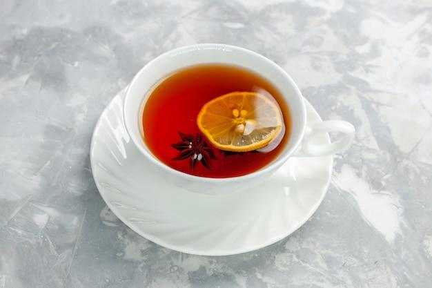 Чашка чая с лимоном на белой поверхности, вид спереди