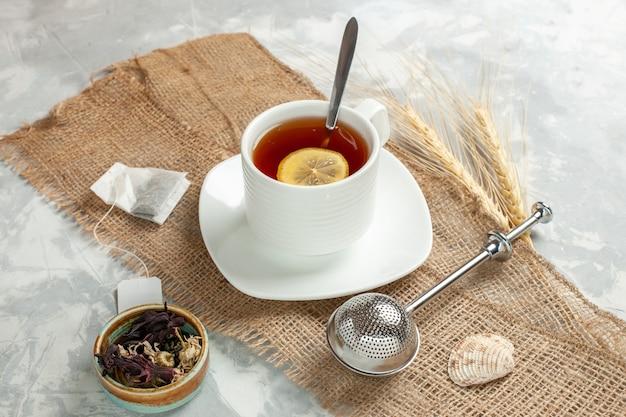Вид спереди чашка чая с долькой лимона на белой поверхности