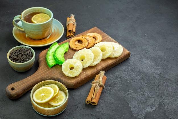 Вид спереди чашка чая с ломтиками лимона и сухофруктами на темной поверхности