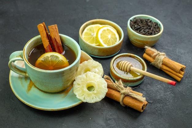 Вид спереди чашка чая с дольками лимона и медом на темной поверхности