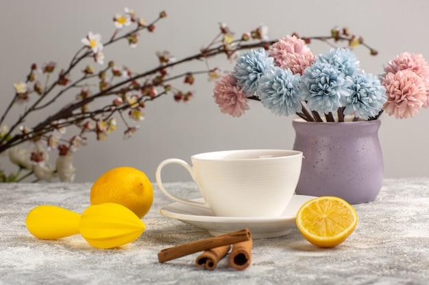 Чашка чая с лимоном и корицей на белом столе, вид спереди