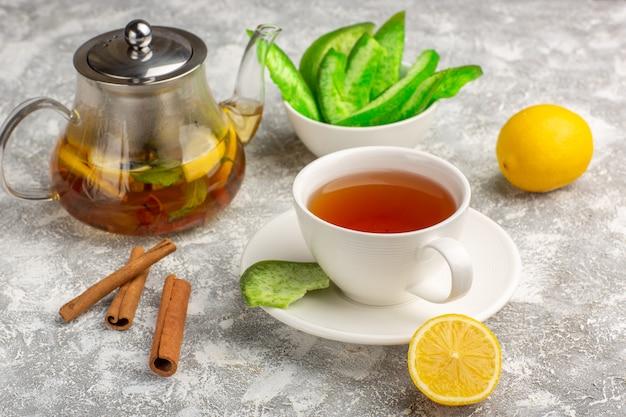 Чашка чая с лимоном и корицей на светло-белой поверхности, вид спереди