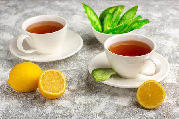 Вид спереди чашка чая с лимонами на светлой белой поверхности