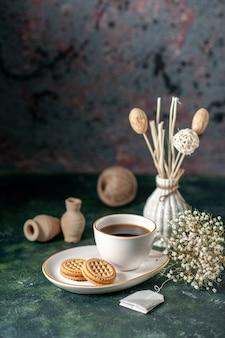 Вид спереди чашка чая с маленьким сладким печеньем в белой тарелке на темной поверхности цветная церемония завтрак утро фото хлеб стакан сахар