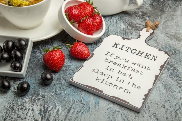 オリーブと面白い机と暗い表面の朝の朝食の食べ物とお茶の正面図