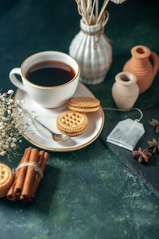 Вид спереди чашка чая со сладким печеньем на темной поверхности хлеб напиток церемония завтрак утро фото цветной сахарный торт стакан