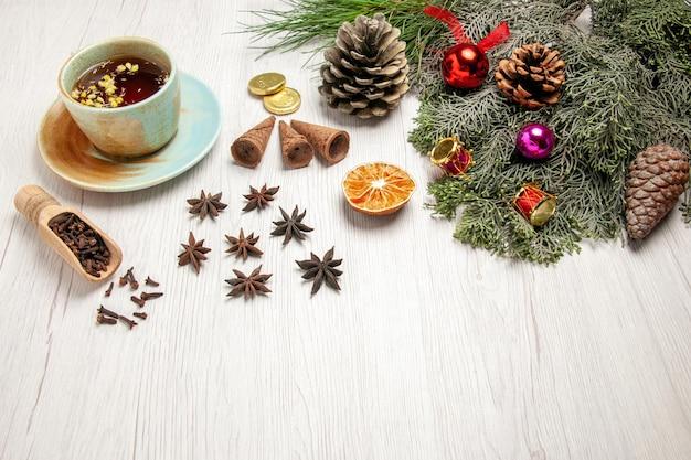 Вид спереди чашка чая с игрушками и деревом на белом столе со вкусом чая