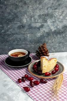 明るい白い表面においしいケーキのスライスとお茶の正面図