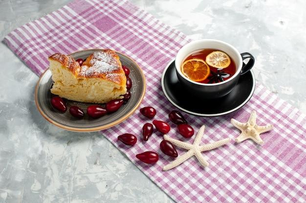 白い表面においしいケーキのスライスとお茶の正面図
