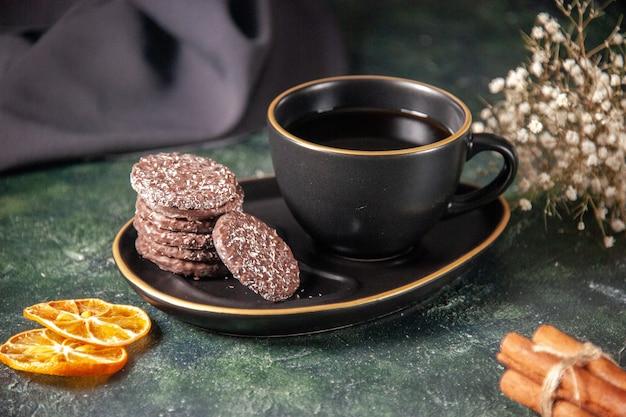 Vista frontale tazza di tè in tazza nera e piatto con biscotti sulla superficie scura colore zucchero cerimonia di vetro colazione dessert torta
