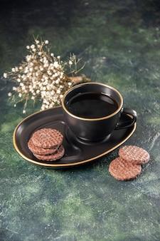 Vista frontale tazza di tè in tazza nera e piatto con biscotti sulla superficie scura colore vetro zucchero prima colazione dessert torta cerimonia