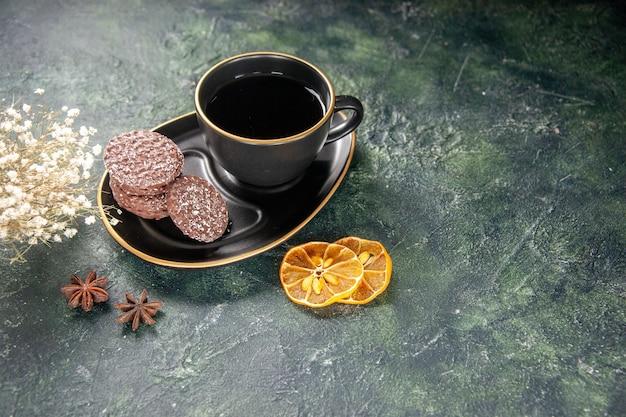 Vista frontale tazza di tè in tazza nera e piatto con biscotti sulla superficie scura colore vetro zucchero colazione dessert torta biscotto spazio libero
