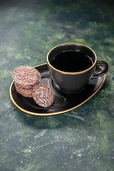 Vista frontale tazza di tè in tazza nera e piatto con biscotti sulla superficie scura colore vetro zucchero prima colazione dessert torta biscotto