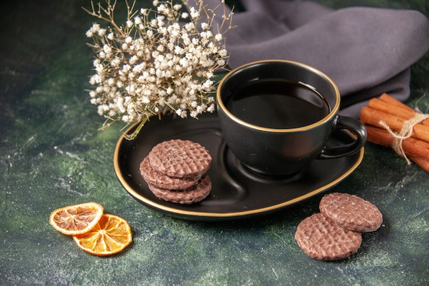 Vista frontale tazza di tè in tazza nera e piatto con biscotti sulla superficie scura colore vetro zucchero prima colazione dessert torta biscotti cerimonia