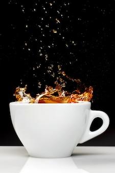 Vista frontale della tazza di tè sulla parete nera