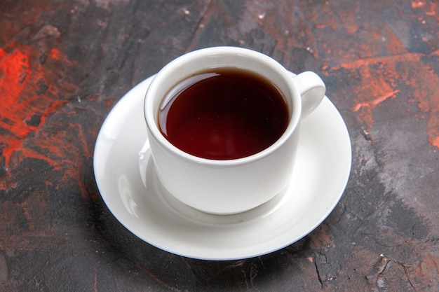 Front view cup of tea on a dark table color dark tea ceremony